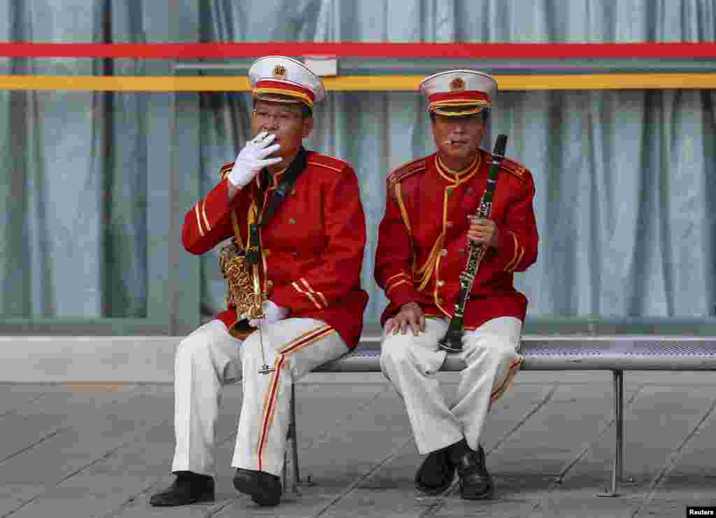 Members of a music band smoke cigarettes on a bench as they take a break, in Kunming, Yunnan province, China. China is set to raise the wholesale tax rate for cigarettes to 11 percent from 5 percent, the Ministry of Finance said in early May, in a move to deter smokers in the world's biggest maker and consumer of tobacco.