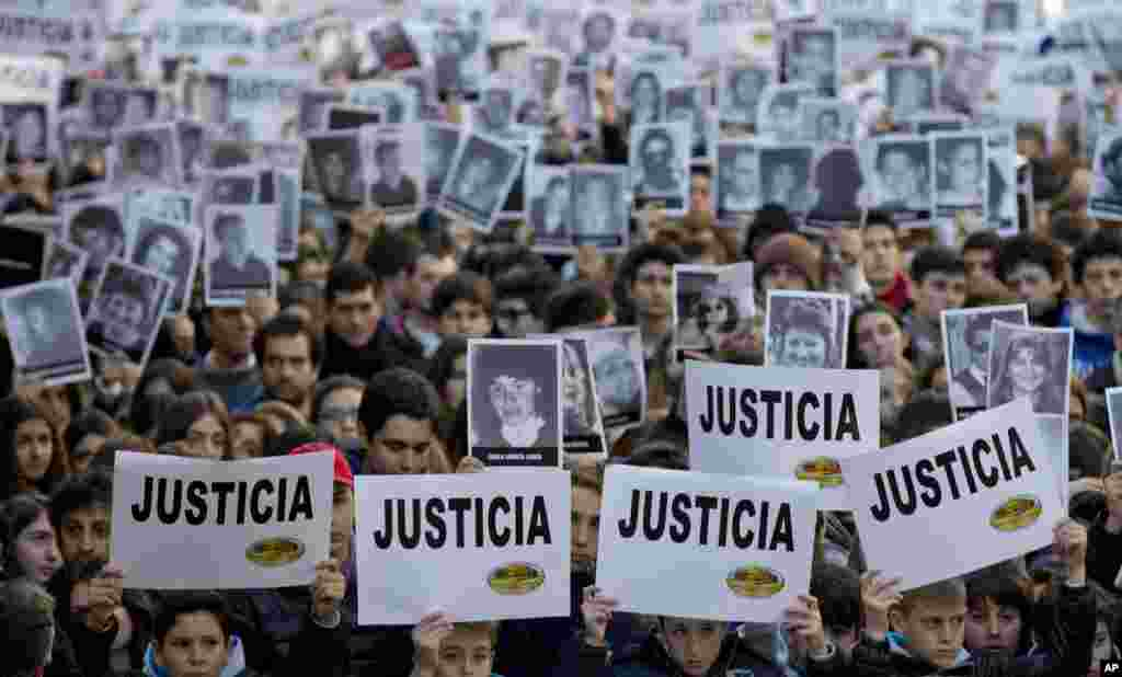 "People hold up signs that read ""Justice"" in Spanish and pictures of the victims of the 1994 bombing of the AMIA Jewish community center during a commemoration ceremony in Buenos Aires, Argentina. Friday marks the 20th anniversary of the unsolved bombing attack that left 85 dead."