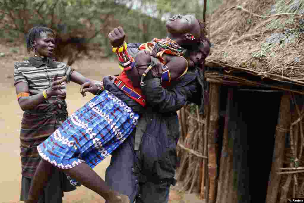 A man holds a girl as she tries to escape when she realized she is to to be married, about 80 km (50 miles) from the town of Marigat in Baringo County, Kenya. As Pokot tradition dictates, the future husband arrived to her family home with a group of men to collect the girl. But the girl was unaware of the marriage arrangements that her father had made. The family said that if they had told her in advance she might have run away from home.