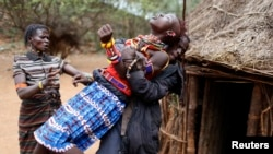 FILE - A man holds a girl as she tries to escape when she realized she is to to be married, about 80 km (50 miles) from the town of Marigat in Baringo County, Dec. 7, 2014.