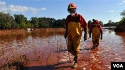 Para petugas penyelamat Hongaria melacak tumpahan lumpur merah dari limbah pabrik aluminium di kota Kolontar untuk mencari kemungkinan adanya korban.