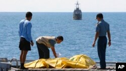 지난 23일 인도네시아 자바해 인근에서 구조 요원들이 에어아시아 소속 사고기 탑승자로 보이는 시신을 수습하고 있다. (자료사진)