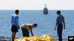 Beberapa anggota Basarnas memeriksa jenazah penumpang korban pesawat AirAsia di atas kapal Angkatan Laut KRI Banda Aceh di Laut Jawa (23/1). (AP/Natanael Pohan)
