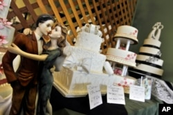 FILE - Figurines are depicted in an embrace as part of the wedding cake display at Masterpiece Cakeshop, Denver, Colorado, June 6, 2013.