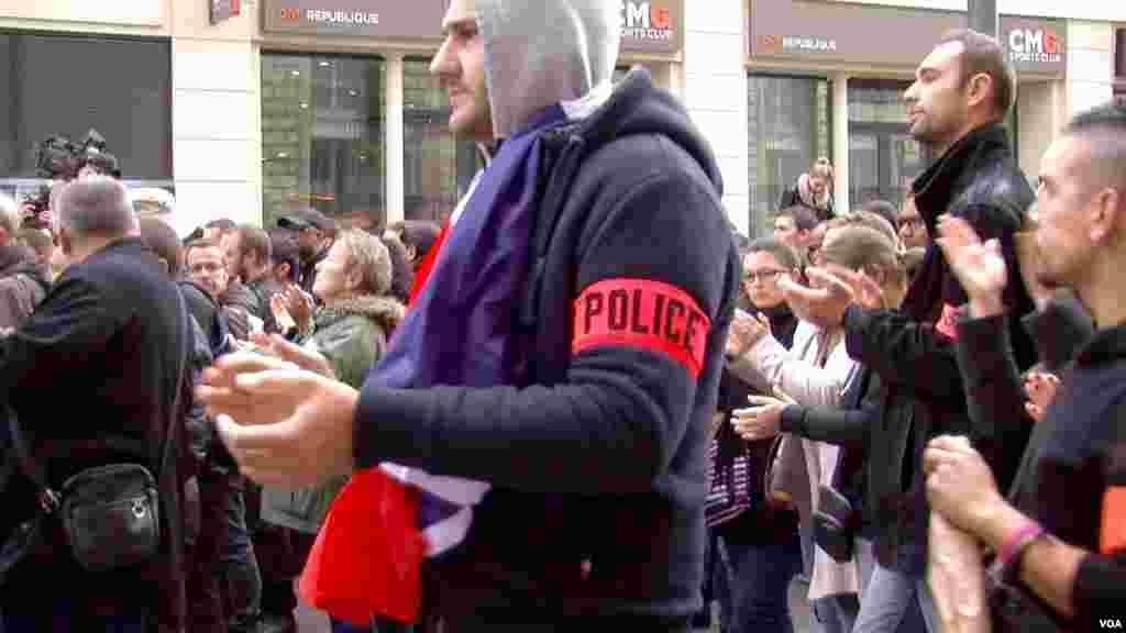 Polisi menyanyikan lagu kebangsaan Perancis dalam demonstrasi damai di Paris (26/10). (VOA/L. Bryant)