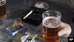 Cigarette packets sporting graphic health pictures lie on a table while workers have a drink a a local pub in Sydney, Australia, July 6, 2011.