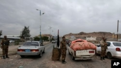 Yemeni soldiers inspect cars at a checkpoint leading to the U.S. embassy in Sanaa, Yemen, Aug. 4, 2013, one of 21 U.S. diplomatic missions ordered closed for the weekend due to the threat of an al-Qaida attack.