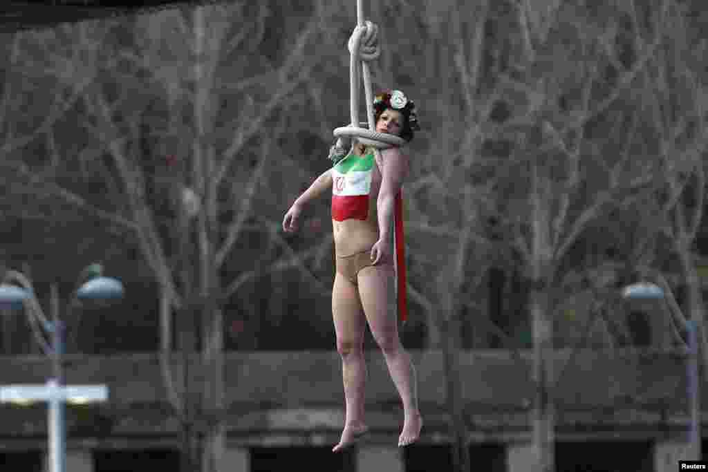یک زن نیمه برهنه، از گروه فمن ها که معمولا اعتراض خود را با برهنگی انجام می دهند، در حالیکه پرچم جمهوری اسلامی ایران را بر روی سینه خود نقاشی کرده، به شکل نمادین خود را حلق آویز کرده است. اشاره او به آمار بالای اعدام ها در ایران است.