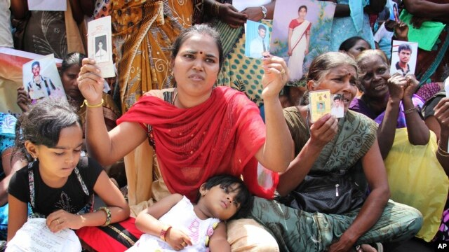 Family members of disappeared Tamil people holding pictures of their relatives protest during the visit of U.N. High Commissioner for Human Rights Navi Pillay, in Jaffna, Sri Lanka, Aug. 27, 2013.