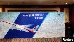FILE - A policeman takes a nap beside a board written with messages for passengers onboard the missing Malaysia Airlines Flight MH370 during a closed meeting held between Malaysian representatives and Chinese relatives of passengers on Flight MH370 at Lido Hotel.