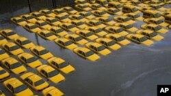 Taksi-taksi terendam oleh luapan air banjir akibat badai Sandy di lapangan parkir di Hoboken, New Jersey (30/10).