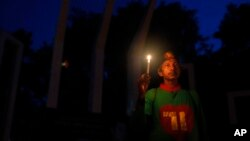 FILE - A Bangladeshi activist holds a candle, as they protest against the killing of secular blogger Niladri Chottopadhay Niloy in Dhaka, Bangladesh, Friday, Aug. 14, 2015.