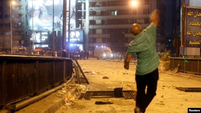 A supporter of deposed Egyptian President Mohamed Morsi throws stones at riot police during clashes in the Ramsis square area in central Cairo, July 15, 2013.