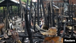 A man walks through a neighborhood that was burnt in recent violence in Sittwe, June 16, 2012.