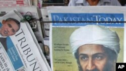 A roadside vendor sells newspapers with headlines about the death of al-Qaeda leader Osama bin Laden, in Lahore May 3, 2011.