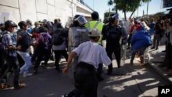 在蒂华纳市的过境点附近,移民们冲破一道警察防线,冲向美墨边境(2018年11月25日)