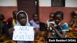 "FILE - A young displaced Muslim girl holds a sign saying ""No to Violence"" at a displaced persons site, the Catholic church in Bangassou, Central African Republic."