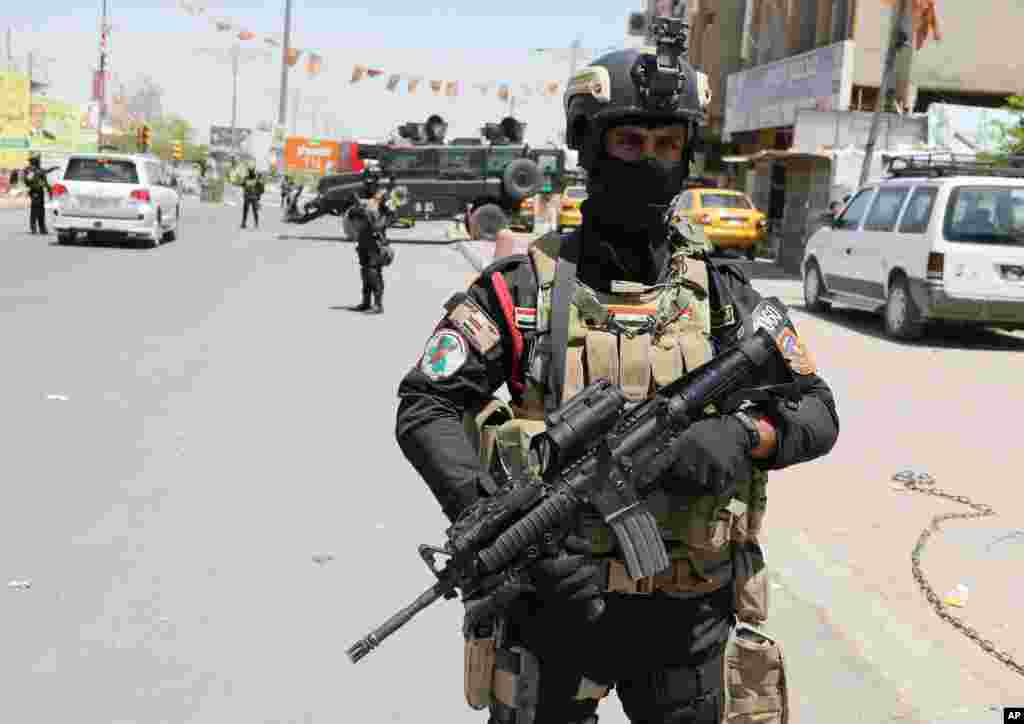 A member of Iraq's Special Weapons and Tactics Team (SWAT) stands guard in front of a polling station in Baghdad, April 30, 2014.