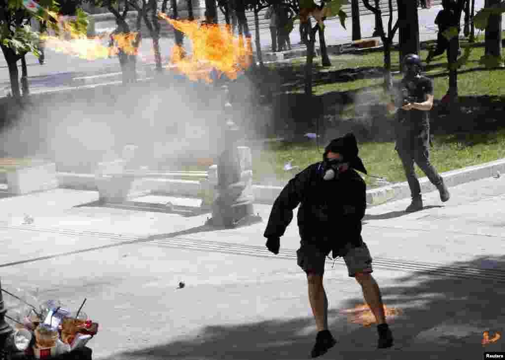 ຜູ້ປະທ້ວງຄົນນຶ່ງແກວ່ງລະເບີດ molotov cocktail ຫລື ລະເບີດໄຟ ໃສ່ຕໍາຫລວດປາບຈະລາຈົນ ຢູ່ໃກ້ຈະຕຸລັດ Syntagma ໃນລະຫວ່າງການນັດຢຸດງານປະທ້ວງ ເປັນເວລາ 24 ຊົ່ວໂມງ ໃນນະຄອນຫລວງ Athens, ວັນທີ 26 ກັນຍາ 2012.