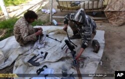 FILE - In this file photo released on June 16, 2015, by Islamic State militant group supporters on an anonymous photo sharing website, Islamic State militants clean their weapons in Deir el-Zour city, Syria.