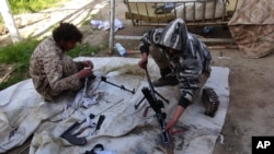 FILE - In this file photo released June 16, 2015, by Islamic State supporters on a photo-sharing website, IS militants clean their weapons in Deir el-Zour, Syria. Militants on Saturday seized territory in the city, which is split between government forces and IS fighters.