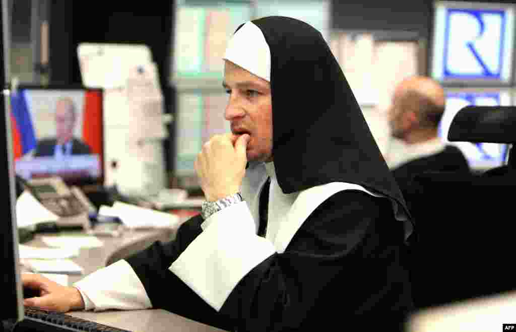 A stock trader dressed up as nun works at the traditional stock exchange carnival in Frankfurt, Germany.