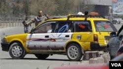 Seorang penjaga keamanan mengamankan lalu-lintas setelah terjadi serangan di dalam gedung Kementerian Pertahanan di Kabul, Senin (18/4).