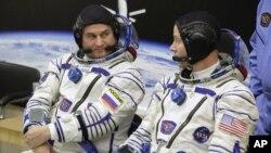 El astronauta estadounidense Nick Hague (derecha) y el cosmonauta ruso Alexey Ovchinin hablan antes de despegar a bordo de una cápsula Soyuz MS-10 hacia la Estación Espacial Internacional, en Baikonur, Kazajistán, el 11 de octubre de 2018. (AP Foto/Dmitri Lovetsky)