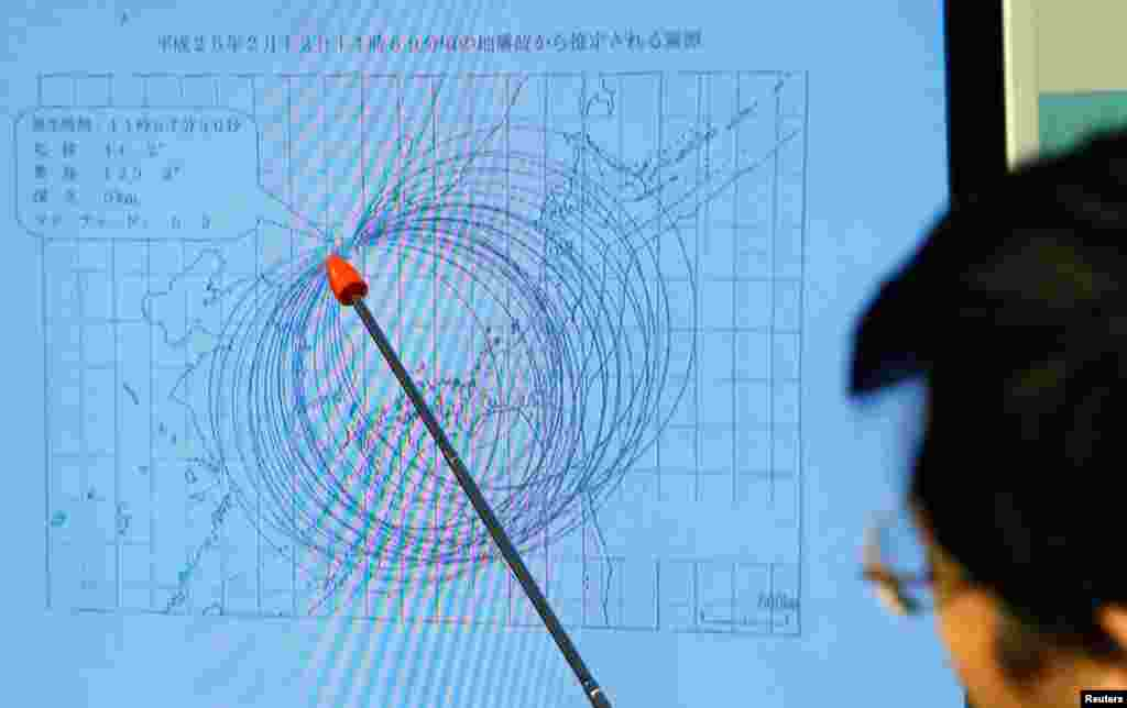 Japan Meteorological Agency's earthquake and tsunami observations division director Akira Nagai points to a spot on the map showing the quake center during a news conference in Tokyo, February 12, 2013.
