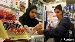 FILE - An Iranian woman tests the colours of make-up at an upscale shop in north Tehran.