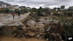 Warga terpaksa harus melewati jalan berlumpur pasca banjir bandang di kota Villanueva del Rosario, Malaga, Spanyol selatan (28/9). Badai tornado dikabarkan melanda kota Gandia dan merusak fasilitas permainan di sebuah pasar malam kota itu.