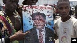 Opposition UDPS members hold up blood-splattered poster of leader Etienne Tshisekedi after presidential guard opened fire on crowd outside N'Djili airport in Kinshasa, November 26, 2011.