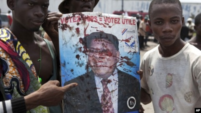 Opposition UDPS members hold up blood-splattered poster of leader Etienne Tshisekedi after presidential guard opened fire on crowd outside N'Djili airport in Kinshasa, November 26, 2011.