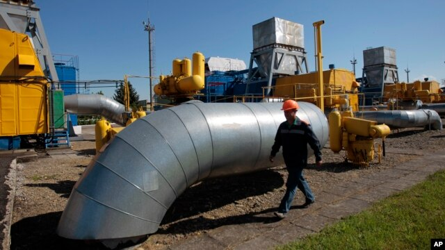 A gas pipeline station worker passing the gas pressure engines in Bil 'che-Volicko-Ugerske underground gas storage facilities in Strij, outside Lviv, Ukraine, May 21, 2014.