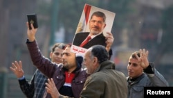 FILE - Supporters of the Muslim Brotherhood and ousted Egyptian President Mohammed Morsi hold a copy of the Koran and Morsi's picture at Talaat Harb Square, in Cairo, Jan. 25, 2015.
