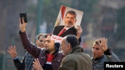 穆斯林兄弟会的支持者在广场上手持可兰经和被罢黜的穆尔西总统的肖像