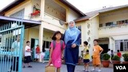 Seorang ibu menjemput anaknya pulang dari taman kanak-kanak di sebuah wilayah di Sarawak di mana bahasa ibu dipergunakan dalam program pengajaran, bukan bahasa Melayu.