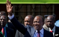 FILE - Kenya's President-Elect Uhuru Kenyatta gestures to supporters as he leaves the National Election Center where final election results were announced declaring he would be the country's next president, in Nairobi, March 9, 2013.