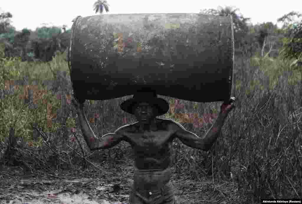 Nigéria: Ebiowei, 48 anos, carrega um barril de petróleo vazio para poder ser reabastecido numa refinaria ilegal