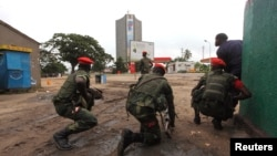 Congolese security officers position themselves as they secure the street near the state television headquarters in the capital Kinshasa, DRC, Dec. 30, 2013.