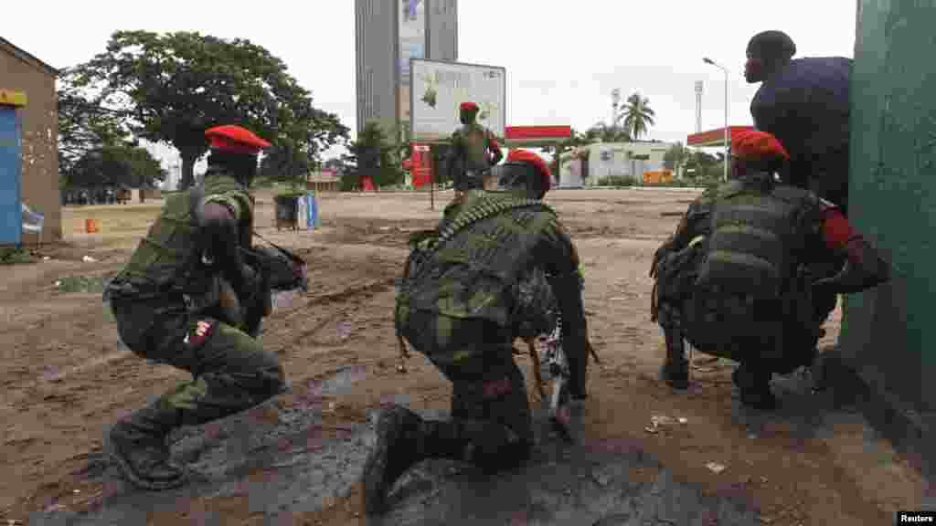 Des agent des forces de l'ordre prennent position, arme à la main et prête à être utilisée, lors d'une émeute à Kinshasa prêt de la télévision nationale congolaise, le 30 décembre 2013. REUTERS/Jean Robert N'Kengo.