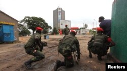 Congolese security officers position themselves as they secure the street near the state television headquarters (C) in the capital Kinshasa, DRC, Dec. 30, 2013.