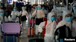 Chinese students living in Thailand wear protective suits as a measure of protection against the coronavirus disease (COVID-19) as they walk at the Suvarnabhumi Airport before boarding a repatriation flight, in Bangkok, Thailand April 21, 2020.