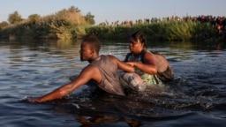 Para migran, yang kebanyakan berasal dari Haiti, menyeberangi sungai Rio Grande di Del Rio, Texas, untuk menuju kota Ciudad Acuña, Meksiko, apad 20 September 2021. Upaya tersebut dilakukan untuk menghindari deportasi yang dilakukan oleh pemerintah AS. (Foto: AP/Felix Marquez)