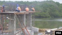Para pekerja pembangunan badan jalan di atas perairan di kawasan hutan bakau Taman Hutan Raya Ngurah Rai, Bali. (VOA/Muliarta)