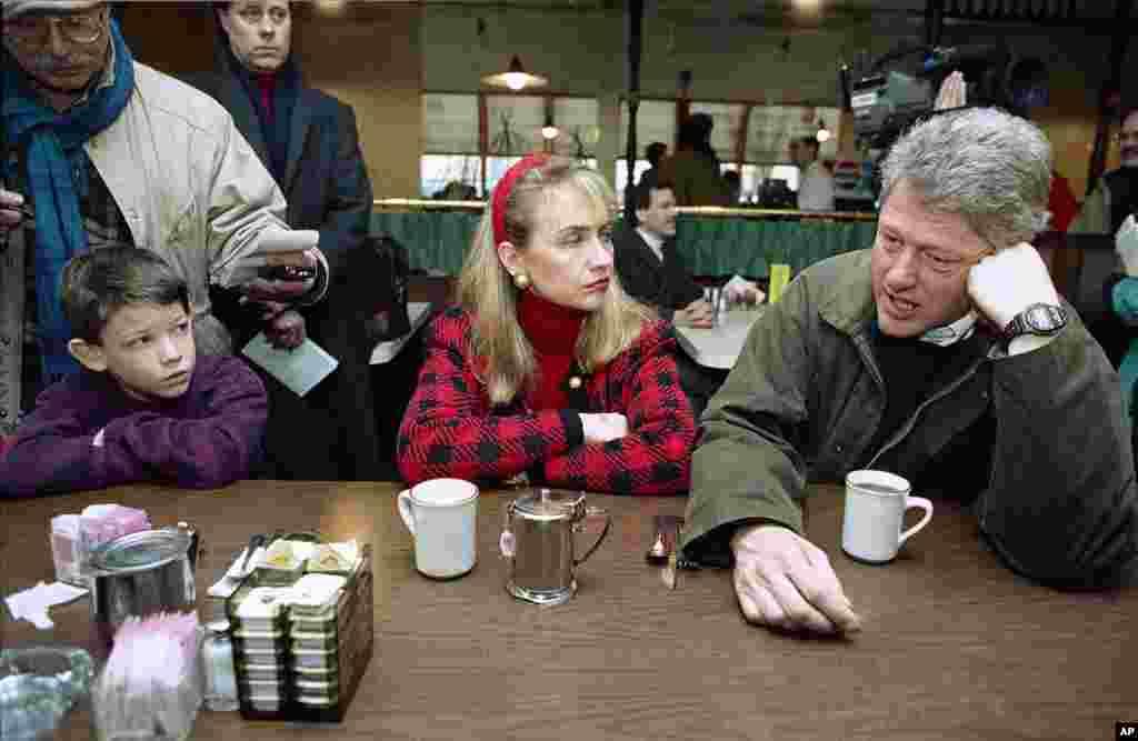 អភិបាលរដ្ឋ Arkansas លោក Bill Clinton ជាមួយនឹងភរិយាលោកស្រី Hillary Rodham ចូលទទួលទានកាហ្វេនៅភោជនីយដ្ឋាន Blake's Restaurant ក្នុងក្រុង Manchester រដ្ឋ New Hampshire កាលពីថ្ងៃសៅរ៍ ទី១៥ ខែកុម្ភៈ ឆ្នាំ១៩៩២ មុនពេលធ្វើយុទ្ធនាការឃោសនាបោះឆ្នោត។