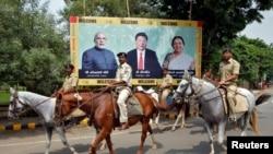 La police patrouille sur des chevaux devant une affiche avec l'image du Premier ministre Narendra Modi Inde, du président Xi Jinping de la Chine et du ministre en chef de l'État indien de Gujarat Anandiben Patel, à Ahmedabad, Inde, 16 septembre 2014.