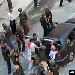 An grab taken on June 27, 2011 from footage uploaded on YouTube on June 24 allegedly shows Syrian security forces beating two men with batons and shoving them in the trunk of a car in Barza on the outskirts of Damascus (editorial content, date and locatio