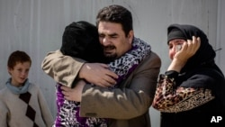 Balkis, 15, embraces her father, Sheikh Matar, March 31, 2016. after being separated from him for over a year. Balkis stayed with her mother, younger sister, and two younger brothers in Islamic State group-controlled territory after her father was forced to the Kurdish north.