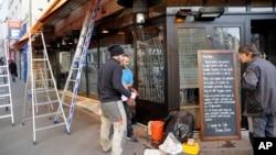 """Beberapa orang pria tengah memperbaiki bagian depan cafe """"La bonne biere"""", yang menjadi target serangan teroris di Paris, bulan November 2015 (3/12)."""